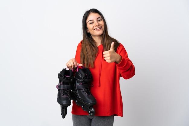 親指を立てるジェスチャーを与える白い壁に分離された若いスケーターの女性