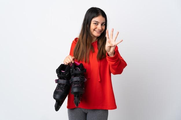 Молодая фигуристка изолирована на белой стене счастлива и считает четыре пальцами