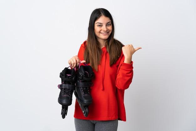 製品を提示する側を指している白い壁に分離された若いスケーターの女性