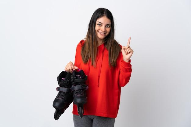素晴らしいアイデアを指している白い壁に孤立した若いスケーターの女性