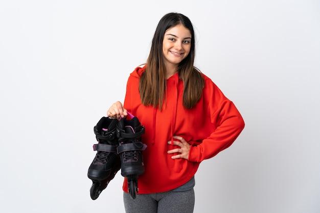 腰に腕と笑顔でポーズをとって白い壁に分離された若いスケーターの女性
