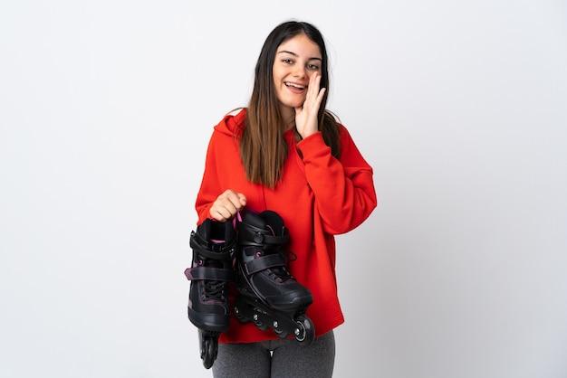 口を大きく開いて叫んで白い壁に孤立した若いスケーターの女性
