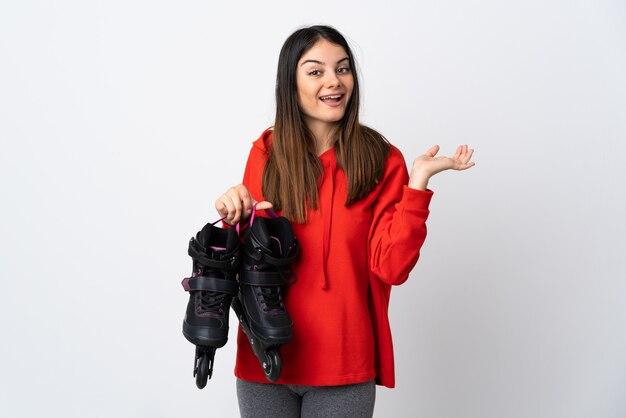 ショックを受けた表情で白い壁に分離された若いスケーターの女性
