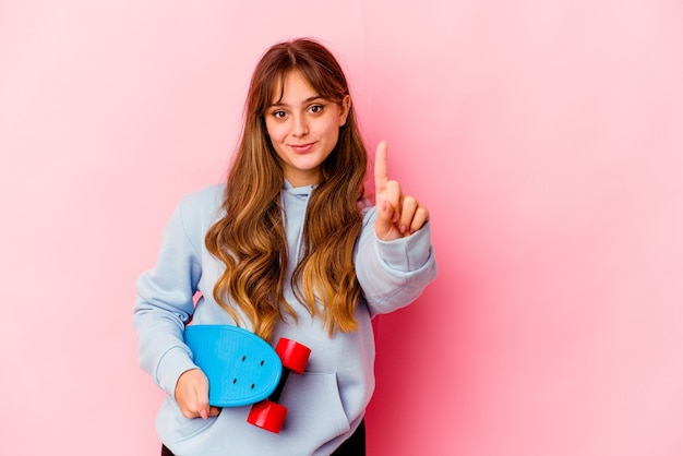 Young skater woman isolated on pink background showing number one with finger.