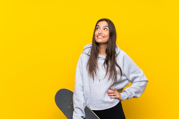 Young skater woman  isolated on yellow  looking up while smiling
