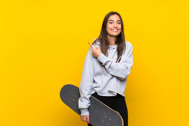 Young skater woman over isolated yellow wall pointing to the side to present a product