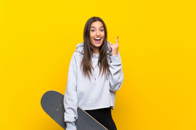 Young skater woman over isolated yellow wall pointing up a great idea