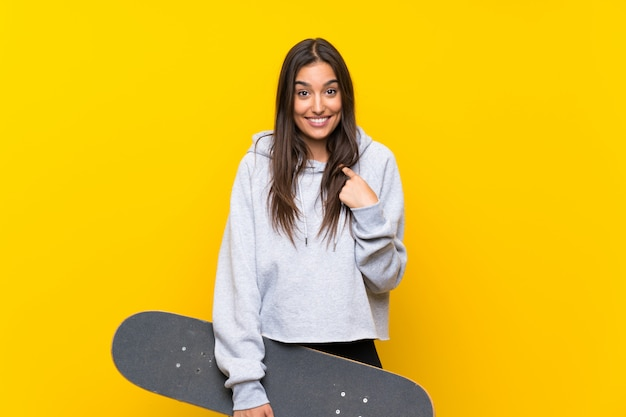 Young skater woman over isolated yellow wall with surprise facial expression