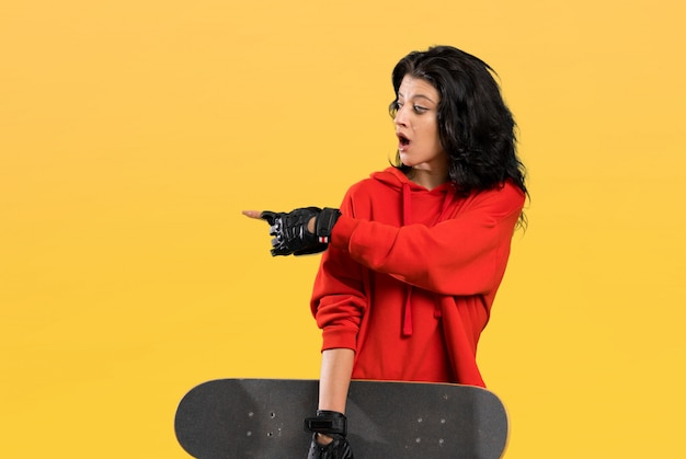 Young skater woman surprised and pointing side  isolated