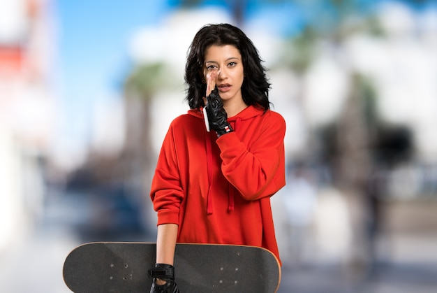 Young skater woman whispering something at outdoors