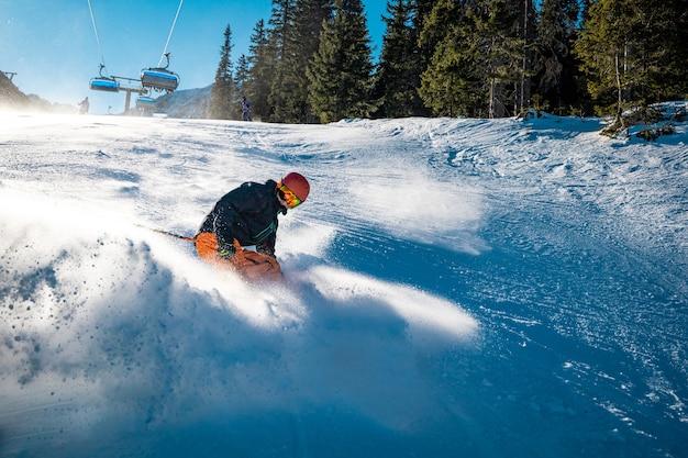 Молодой лыжник тормозит с улыбкой на лице