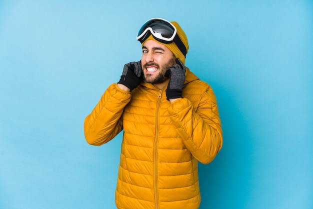 Young skier caucasian man isolated covering ears with hands.