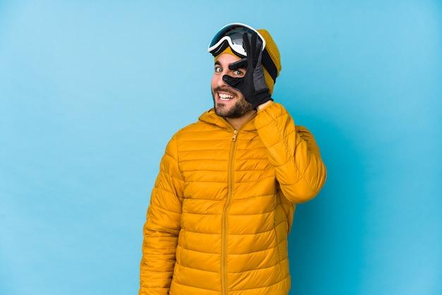 若いスキーヤーの白人男性は、目で大丈夫なジェスチャーを維持して興奮して孤立しました。