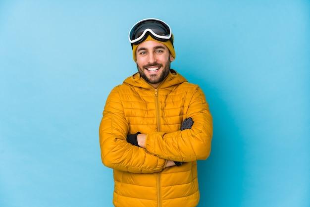 Кавказский человек молодой лыжник изолированы смеясь и весело.