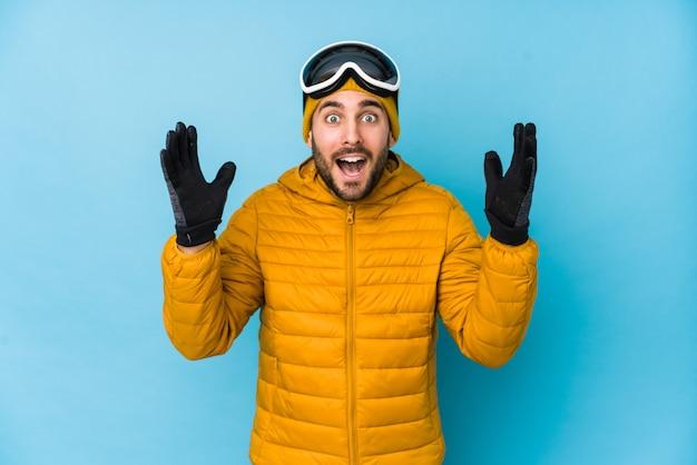 Кавказский человек молодого лыжника изолировал получая приятный сюрприз, взволновал и поднял руки.