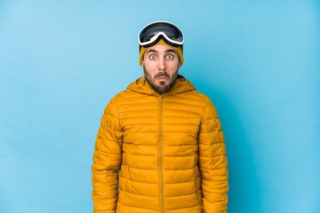 Молодой лыжник кавказский изолировал пожимает плечами плечами и смущает открытые глаза.