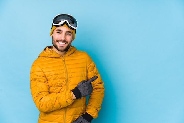Молодой лыжник кавказский человек изолировал улыбаясь и указывая в сторону, показывая что-то на пустом месте.