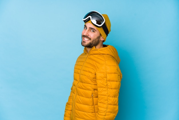 Young skier man isolated looks aside smiling, cheerful and pleasant