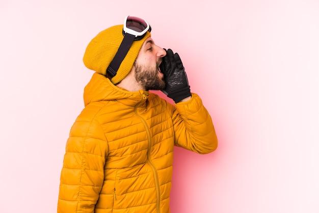 Молодой лыжник изолировал кричать и держать ладонь возле открытого рта.