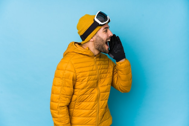Young skier man isolated shouting and holding palm near opened mouth