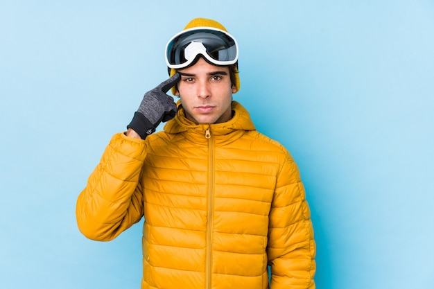 Young skier man wearing snowboard goggles isolated showing a disappointment gesture with forefinger.