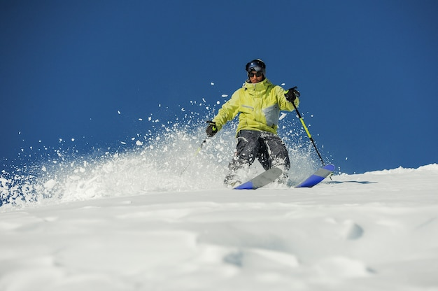 Young skier in yellow sportswear riding down the slope in georgia, gudauri