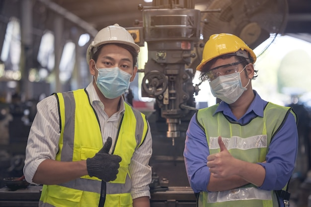 若い熟練した工場労働者またはエンジニアが工場で肖像画をクローズアップ