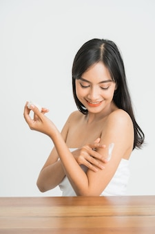 Young skin care asian woman applying body lotion on arm and shoulder