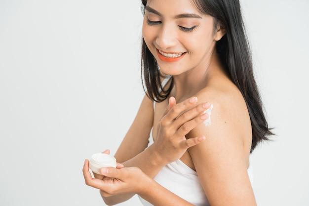 Молодая женщина ухода за кожей азиатская, применяя лосьон для тела на руке и плече