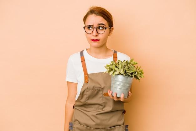 Молодая тощая арабская женщина-садовник смущена, чувствует себя сомнительно и неуверенно
