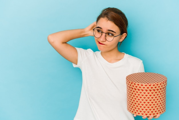 Молодая тощая арабская девушка держит коробку дня святого валентина, касаясь затылка, думая и делая выбор.