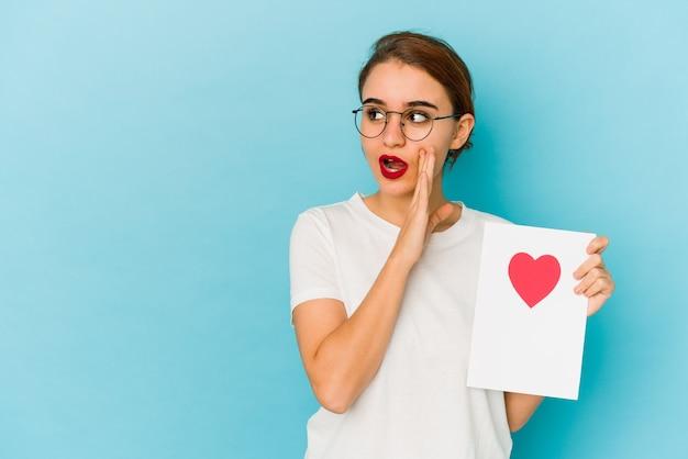 バレンタインデーのカードを持っている若い細いアラブの女の子は、秘密のホットブレーキニュースを言って脇を見ています