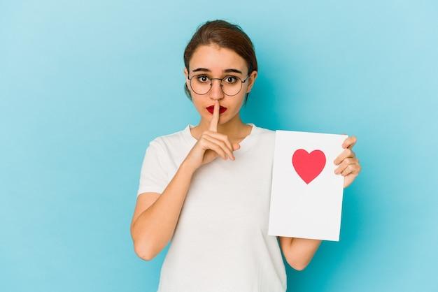 秘密を守るか、沈黙を求めるバレンタインデーカードを持っている若い細いアラブの女の子。