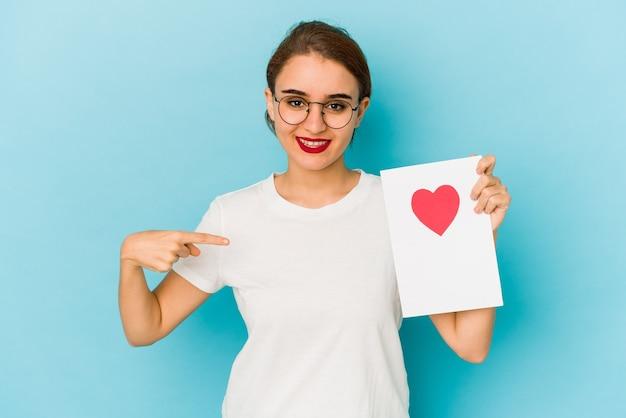バレンタインデーカードの人がシャツのコピースペースを手で指している、誇りと自信を持って若い細いアラブの女の子
