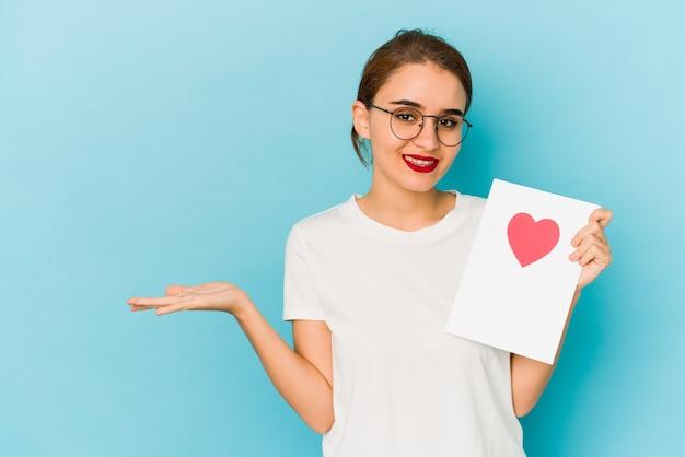 手のひらにコピースペースを示し、腰に別の手を保持しているバレンタインデーカードを保持している若い細いアラブの女の子。
