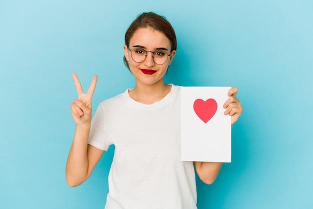指で2番目を示すバレンタインデーカードを保持している若い細いアラブの女の子。