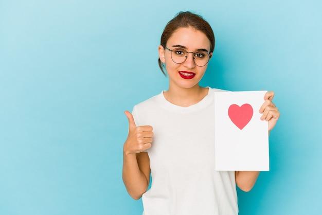 笑顔と親指を上げてバレンタインデーカードを保持している若い細いアラブの女の子