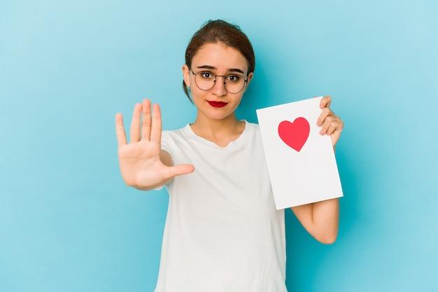 手を伸ばして一時停止の標識を示して立っているバレンタインデーカードを持っている若い細いアラブの女の子は、あなたを防ぎます。