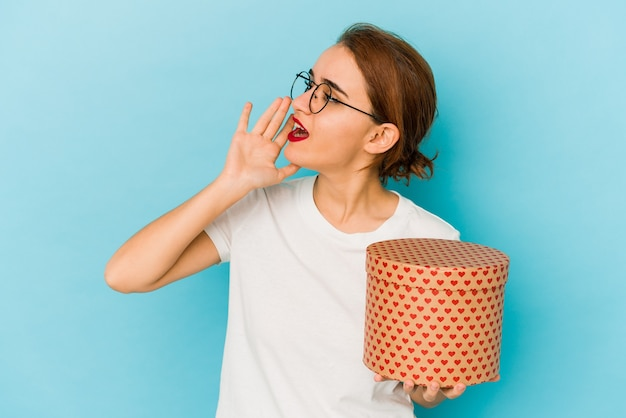 Young skinny arab girl holding a valentines day box shouting and holding palm near opened mouth.