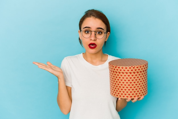 Young skinny arab girl holding a valentines day box surprised and shocked.