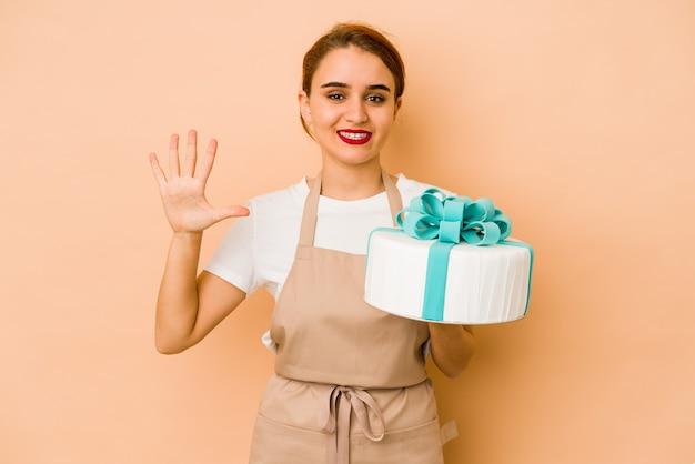 若いスキニーアラブのパティシエの女性は、指で5番を示して陽気な笑顔をしています。