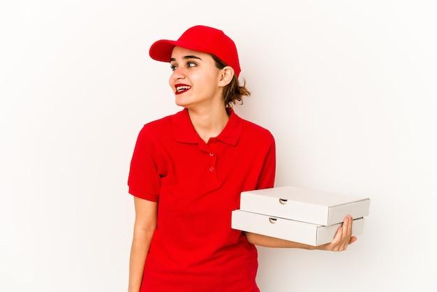 指で平和のシンボルを示す、楽しくてのんきな若い細いアラブのピザ配達の女の子。