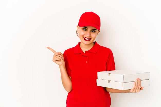Young skinny arab pizza delivery girl looks aside smiling, cheerful and pleasant.