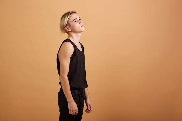 Young skinny blond guy dressed in a black tank top and pants posing in the studio on the beige background .