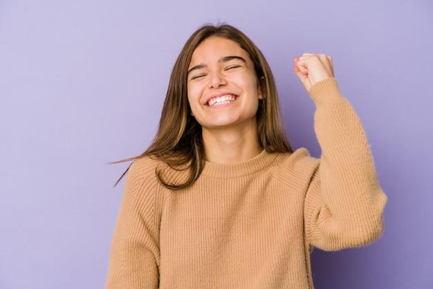 勝利、情熱と熱意、幸せな表現を祝う紫色の背景の若い細い白人の女の子のティーンエイジャー。