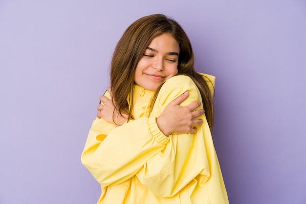 Молодая тощая кавказская девушка-подросток на фиолетовом фоне обнимает, беззаботно улыбается и счастлива.