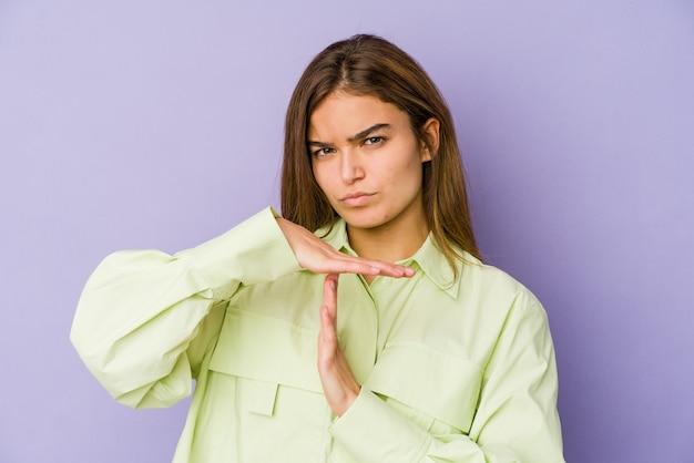 Молодая тощая кавказская девушка-подросток на фиолетовом фоне, показывающая жест тайм-аута.