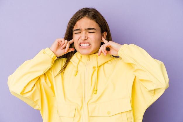 Молодая тощая кавказская девушка-подросток на фиолетовом покрытии ушей пальцами, подчеркнутая и отчаявшаяся из-за громкой окружающей среды.
