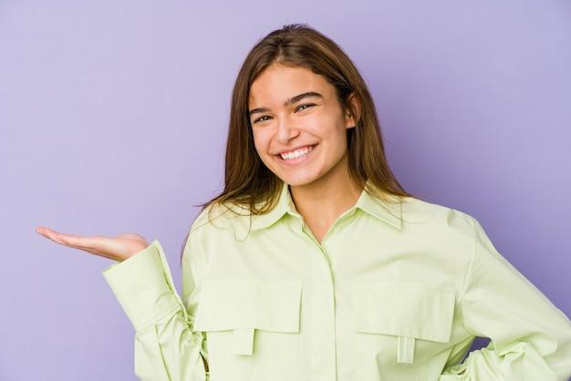 手のひらにコピースペースを示し、腰に別の手を保持している紫色の若い細い白人の女の子のティーンエイジャー。