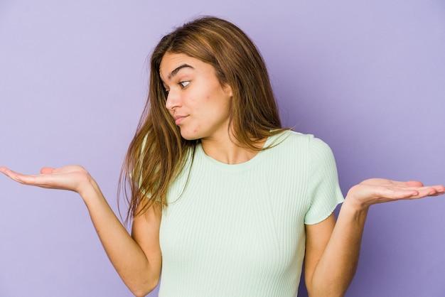 紫色のスペースにいる若い細い白人の女の子のティーンエイジャーは、コピースペースを保持するために混乱し、肩をすくめるのではないかと疑っています。